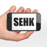 股市标注概念:拿着有SEHK的手智能手机在显示 库存照片