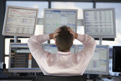 股票交易商观看的屏幕用在头的手 免版税库存照片