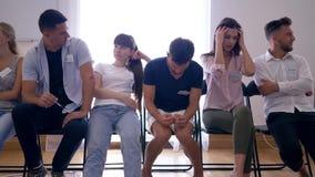 肢体语言,小组用坐在行的不同的情感的青年人在椅子在采访中 股票录像