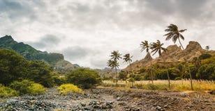 肥沃绿色山谷和坚固性峭壁围拢的干小河全景  圣安唐岛, Cabo Verde 免版税库存图片
