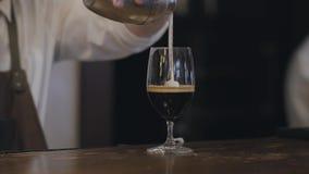 肥满在玻璃的侍酒者倾吐的牛奶与酒精和咖啡使用特定工具,因此它的女性访客的 股票录像