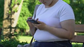 肥满女孩在公园卷动页坐智能手机,聊天与朋友 影视素材