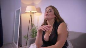 肥满性感的豪华白种人特写镜头射击女性与看照相机的大乳房微笑和摆在户内  股票录像
