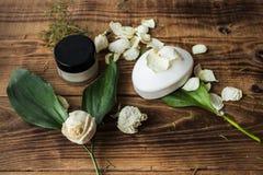 肥皂和奶油与花在木背景 免版税图库摄影