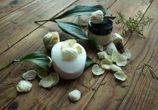 肥皂和奶油与花在木背景 免版税库存照片