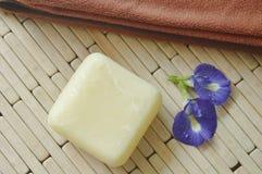 肥皂和毛巾与蓝色豌豆紫罗兰色花在竹席子 库存照片