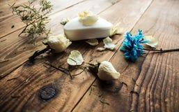 肥皂和白色玫瑰和紫罗兰在木背景 免版税库存照片