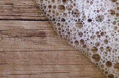 肥皂泡沫和水背景在木头,宏指令起泡 图库摄影