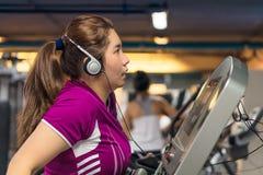 肥胖亚裔妇女在踏车艰苦行使 免版税库存照片