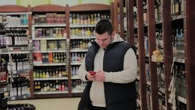 肥胖人在超级市场是在与酒精的部门和神色入电话 股票录像