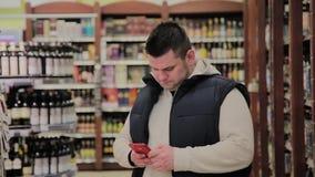 肥胖人在超级市场是在与酒精的部门和神色入电话 影视素材