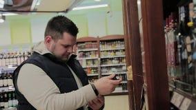肥胖人在超级市场选择他自己的酒精 股票视频