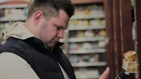 肥胖人在超级市场选择他自己的酒精 影视素材