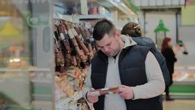 肥胖人在超级市场选择他自己的香肠 股票视频