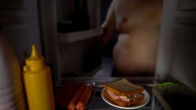 肥胖人打开冰箱门在晚上,饮食失败,瘾吃三明治 免版税库存照片