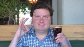肥胖人拿着一杯在咖啡馆和显示好姿态的饮料可乐对照相机 股票录像