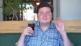 肥胖人拿着一杯在咖啡馆和问候的饮料可乐,问好通过摇手 股票录像