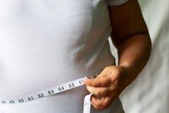 肥胖人检查您的油脂与一卷测量的磁带白色或肥胖病背景 库存照片