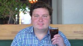 肥胖人通过摇头拿着玻璃在咖啡馆的饮料可乐和同意 股票视频