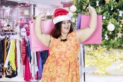 肥胖在购物中心的妇女运载的圣诞节礼物 库存照片