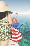 肥胖在跳船的妇女运载的袋子 库存图片