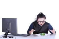 肥胖女实业家要吃硬花甘蓝 免版税库存照片