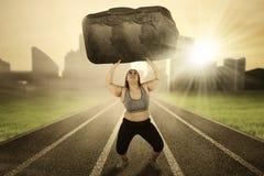 肥胖女性举在轨道的石头 免版税库存照片