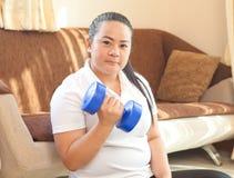 肥胖妇女做与哑铃的健身 免版税库存图片