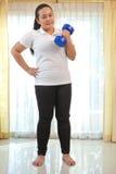 肥胖妇女做与哑铃的健身 免版税库存照片