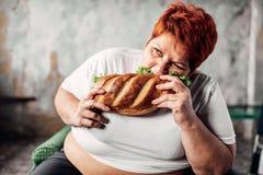 肥胖妇女吃三明治,超重和饥饿 库存图片