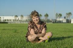 肥胖妇女坐绿草 免版税库存照片