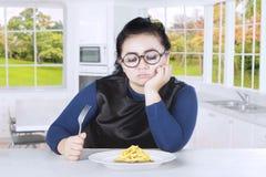 肥胖妇女感觉乏味用炸薯条 免版税库存图片