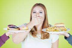肥胖妇女拒绝高卡路里食物 库存照片