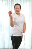 肥胖妇女用苹果 图库摄影