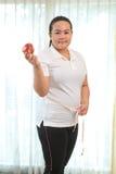 肥胖妇女用苹果 免版税图库摄影