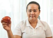 肥胖妇女用苹果 免版税库存图片
