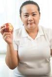 肥胖妇女用苹果 库存图片