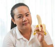 肥胖妇女用香蕉 图库摄影