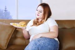 肥胖妇女诱惑用不健康的食物 免版税图库摄影