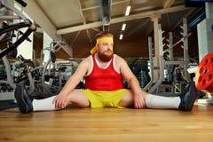肥胖滑稽的人疲倦了坐在健身房的地板 免版税库存照片