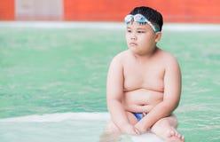 肥胖男孩在游泳池坐 库存照片