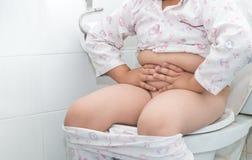 肥胖男孩坐洗手间 免版税库存图片