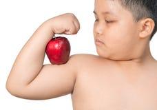 肥胖男孩屈曲他肌肉,当炫耀做的苹果时 免版税图库摄影