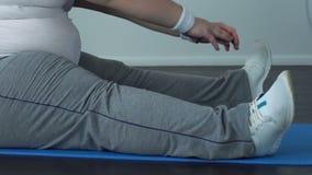 肥胖男性舒展在体育训练,初学者的简单的家庭锻炼前 影视素材