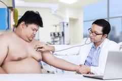 肥胖病人拜访医生对核对 免版税库存照片