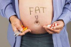 肥胖病的治疗 有在家做胰岛素射入的注射器的肥胖人对他自己 肥胖病健康危害 糖尿病治疗 免版税图库摄影