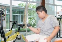 肥胖肥胖男孩举的哑铃在健身屋子里 免版税库存图片