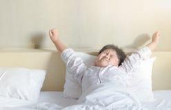 肥胖肥胖男孩醒和舒展 免版税库存图片