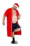 肥腻圣诞老人在一条腿站立 免版税库存图片