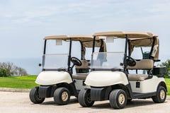 肩并肩停放的空的白色高尔夫车 免版税库存照片